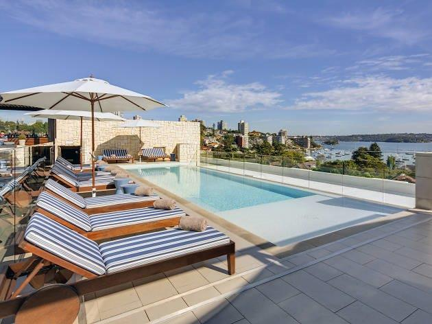 A swimming pool on a rooftop with views out to the city skyline